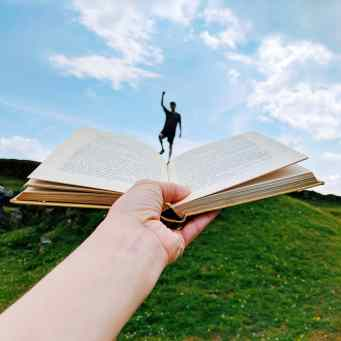 Reader jumping out of a book