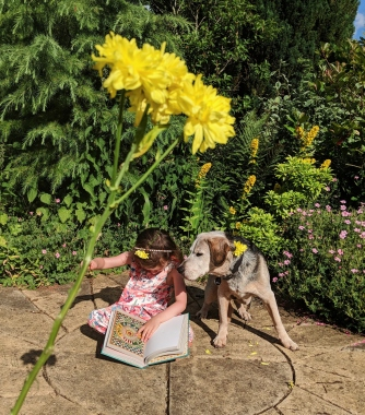 A little girl reading with her dog